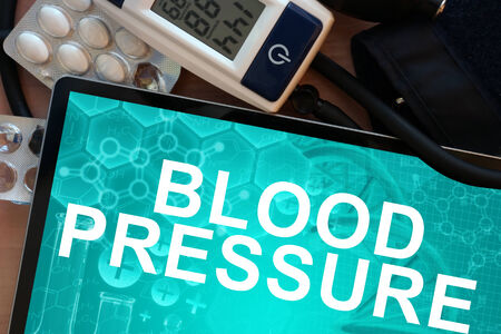 benign: Tablet with the words  blood pressure and Electronic blood pressure monitor