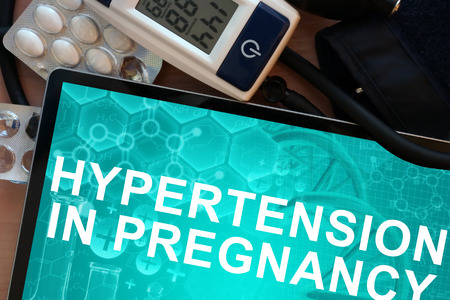 benign: Tablet with the  words Hypertension In Pregnancy and Electronic blood pressure monitor