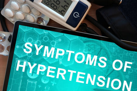 hypertension: Tablet with the  words symptoms of hypertension and Electronic blood pressure monitor Stock Photo