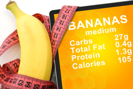 Tablet with Calories In banana and measuring tape on white background. nutrition facts