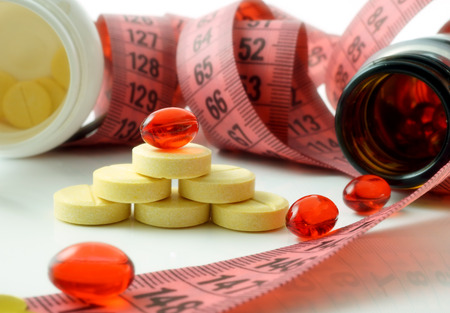 Measuring tape and bottle with pills. supplements of diet