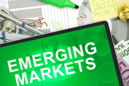 emerging markets: Tablet with words emerging markets with dollars and euro.