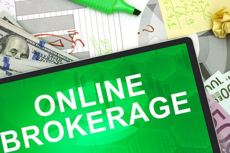 makelaardij: Tablet met woorden Online Makelaars met dollars en euro. Stockfoto