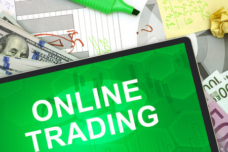 online trading: Tablet with words online trading with dollars and euro. Stock Photo