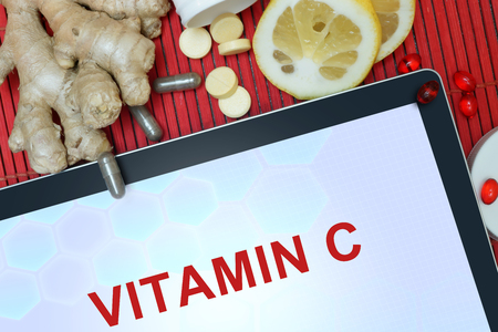 ascorbic: Tablet with words vitamin C, pills, lemon and ginger. Healthy eating. Stock Photo
