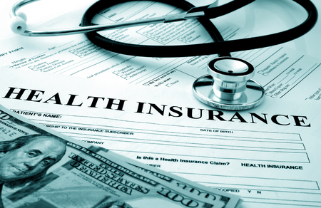 personal injury: Health insurance form with dollars and stethoscope Stock Photo