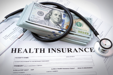 SALUD: Formulario de seguro de salud con dinero y un estetoscopio