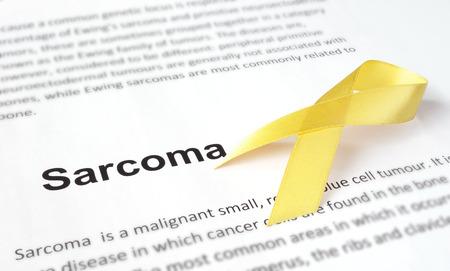 sarcoma: Paper with sarcoma   and yellow ribbon. Stock Photo
