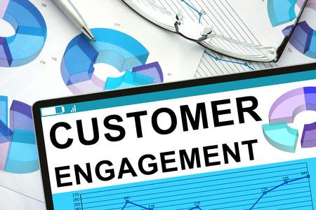 Customer Engagement auf Tablette mit Graphen. Standard-Bild