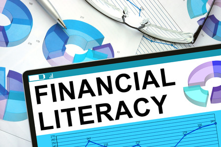 literacy: Financial Literacy  on tablet with graphs. Stock Photo