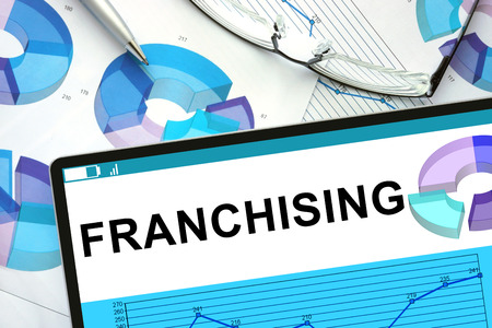 franchising: Franchising  on tablet with graphs.