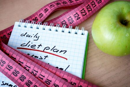 weight loss plan: Notepad with daily diet plan and measuring tape.