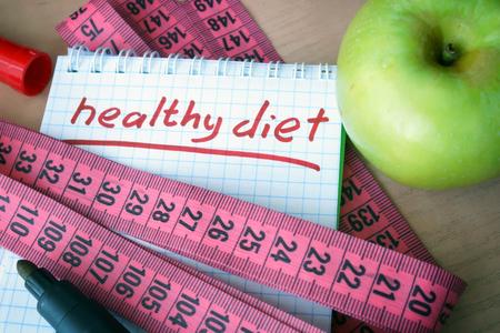 Notatnik ze zdrową dietą i taśmą pomiarową.