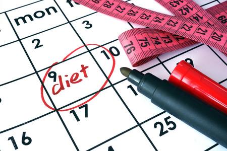 weight loss plan: Calendario con la parola dieta e nastro di misurazione. Archivio Fotografico