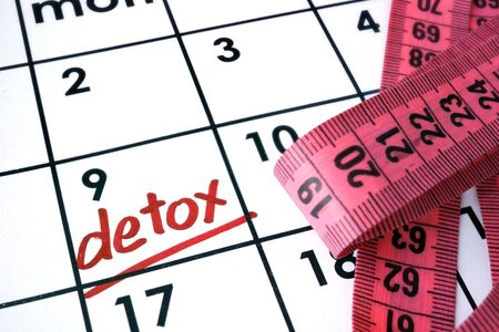 weight loss plan: Calendar with word detox and measuring tape.