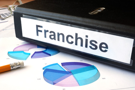 franchise: Graphs and file folder with label  franchise. Stock Photo