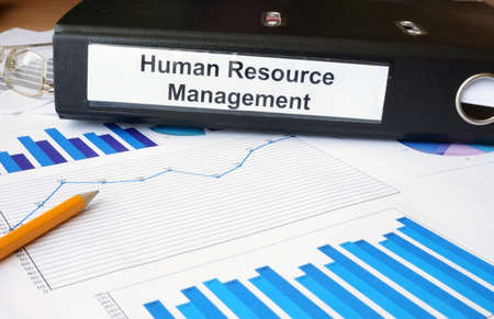 succession planning: Graphs and file folder with label Human Resource Management.