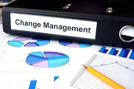change direction: Graphs and file folder with label  Change Management.