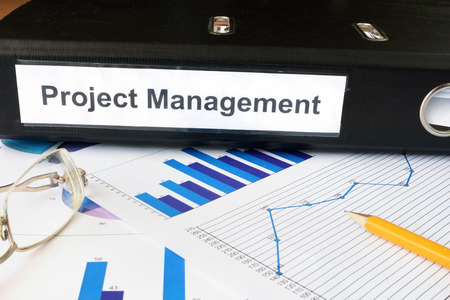 management concept: Graphs and file folder with label  Project Management.