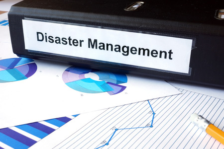 crisis management: Graphs and file folder with label  Disaster Management. Stock Photo