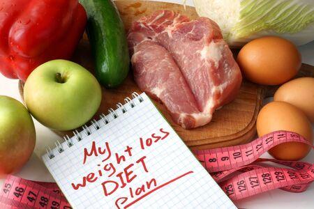 weight loss plan: Blocco note con il piano di perdita di peso dieta e gli alimenti biologici crudi.
