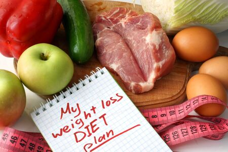 weight loss plan: Notepad  with weight loss diet plan and raw organic food. Stock Photo