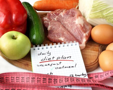 diet plan: Notepad  with diet plan and raw organic food. Stock Photo
