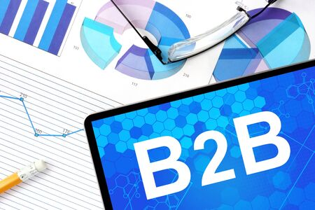 b2b: Tablet with b2b  Business to Business, graphs and glasses. Stock Photo