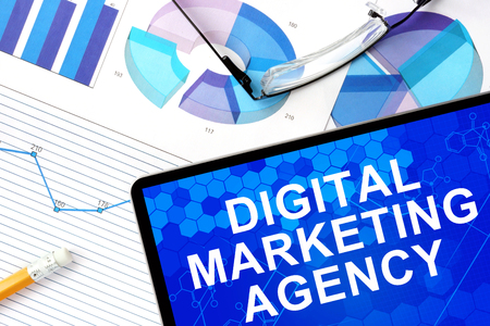 Tablet with digital marketing agency, graphs and glasses.