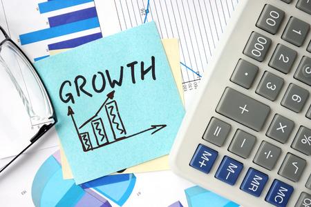 calculadora: Papeles con el concepto de crecimiento de negocio gráficos, calculadora y. Foto de archivo