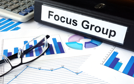 qualitative: File folder with words Focus Group and financial graphs.