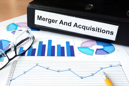 File folder with Merger and Acquisition and financial graphs. Archivio Fotografico