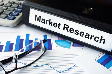 market research: File folder with words Market Research and financial graphs.