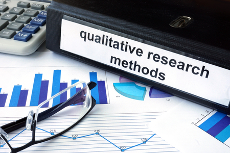 qualitative: File folder with words   qualitative research methods and financial graphs.