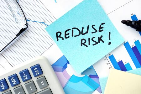 reduce risk: Papers with graphs, glasses and Reduce Risk concept.