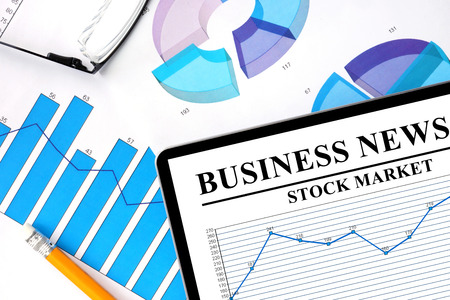 stock news: Tablet with business news of stock market and graphs.