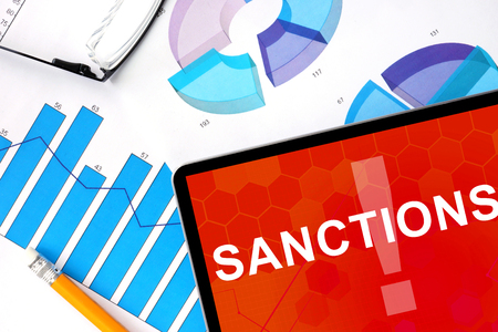 sanctioned: Tablet with word sanctions and graphs.