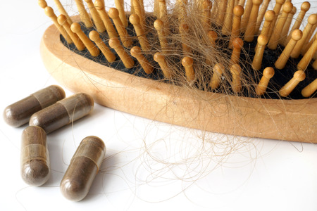 chemotherapy: Pills for hair loss treatment and brush with lost hair on it.