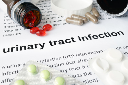 Paper with urinary tract infection and pills. photo