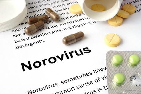 norovirus: Paper with norovirus and pills. Stock Photo