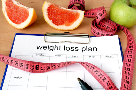 Paper with weight loss plan and grapefruit Stockfoto