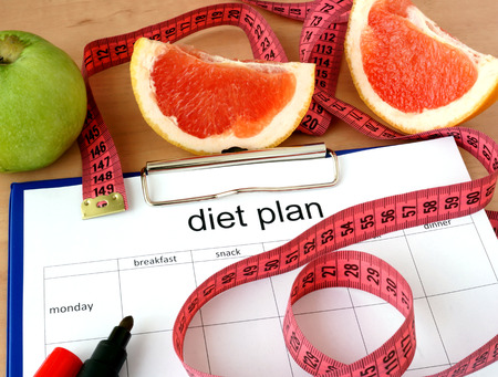 diet plan: Paper with diet plan and grapefruit