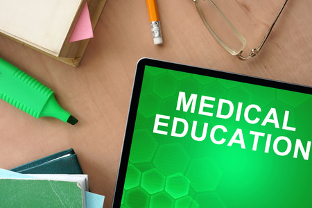 Books and tablet with words Medical Education Stock Photo