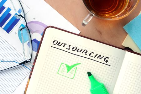 outsourcing: Notepad with word outsourcing concept Stock Photo