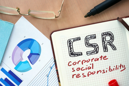 Notepad with word CSR corporate social responsibility concept and marker.