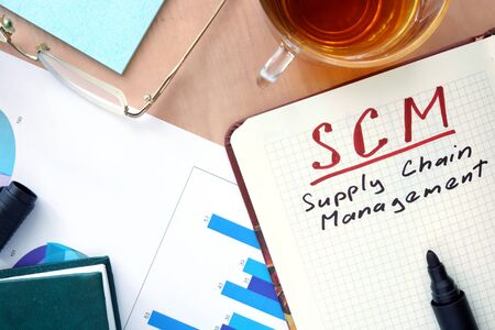 scm: Notepad with words SCM supply chain management concept and marker. Stock Photo