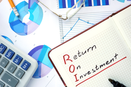financial questions: Notepad with words ROI return on investment concept and marker.