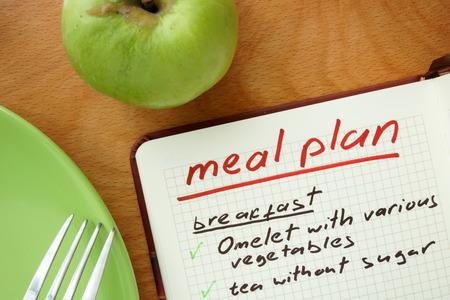 comidas: Bloc de notas con el plan palabras comida con manzana. Concepto de bajar de peso.