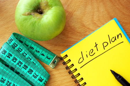 Notepad with words diet plan on a wood board. Weight lose concept. photo