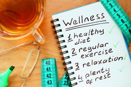 Poznámkový blok s konceptem wellness na dřevěné desce.